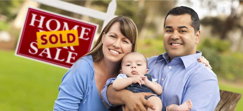 Parents holding child in front of Home Sold sign