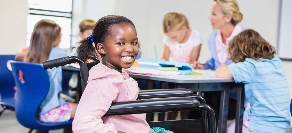 Young girl in chair smiling with class mates in background